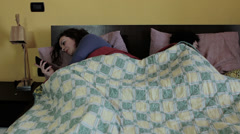 Woman in bed using a mobile phone while sleeping partner: treason, treachery Stock Footage
