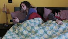 Woman using smartphone in bed: treason, treachery, betrayal Stock Footage
