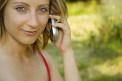 nice girl on the grass-plot with cell phone - stock photo