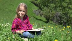 Ultra HD 4K Little Girl Reading Storybook, Student, Child Playing Book on Grass Stock Footage