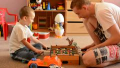 Young man plays with child (small boy) in the room - they play table football - stock footage