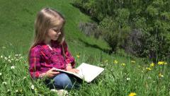 Ultra HD 4K Little Girl Reading Storybook, Student, Child Playing Book on Grass - stock footage