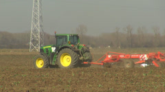 Pan left follow tractor machine plough ground agriculture field land farming day Stock Footage