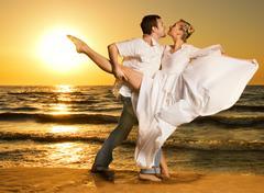Kaunis nuori pari tanssi tangoa rannalla auringonlaskun aikaan Kuvituskuvat