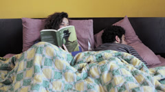 Woman reading book want to play with her partner: bed, love affair, joking Stock Footage