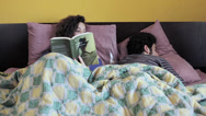 Stock Video Footage of woman reading book want to play with her partner: bed, love affair, joking