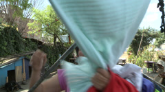 Woman collects washing from line strung across railway track Stock Footage