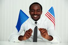 African businessman sitting at the table and holding usa and european flags Stock Photos