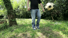 Young man plays with the ball in front of the camera: football, soccer, grass Stock Footage