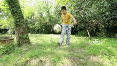 Little boy plays with a ball: football, soccer, outdoor, juggle, feet Stock Footage