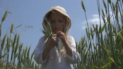 Countrywoman Little Girl Walking in Wheat Field Eating Cereals, Children Playing Stock Footage