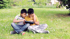 two brothers using tablet computer outside in the garden: grass, sun, games, web - stock footage