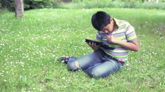 Young boy is using tablet computer in the grass: outdoor, web, games, alone, boy Stock Footage