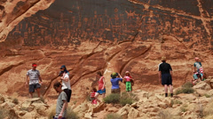 A family looking at petroglyphs indian art Stock Footage
