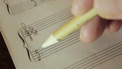 music writing: musician composing with a pencil: staff, key, note, - stock footage