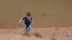 Boy playing in the desert river Stock Footage