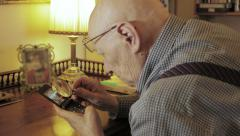 Old man is trying to use cellular phone: low sight, aged, senior, eyesight Stock Footage