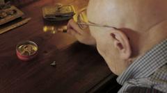 Vanhempi mies käyttää suurennuslasia nähdä jotain hyvin vähän: kappaletta, vanha Arkistovideo