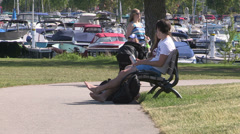 Young People sitting barefoot on park bench on hot summer day in park Stock Footage