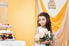 Wistful little lady posing with bouquet of roses Stock Photos