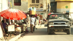 Busy street scene, sellers and cars compete for space Stock Footage