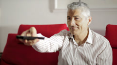 Handsome man typing on remote television control: home, watching tv, living room Stock Footage