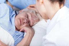 a nurse assists older woman - stock photo