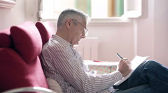 Cute man taking notes sitting on the sofa: writing, pen, window, red, old, home Stock Footage