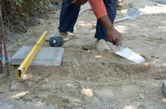 Worker puts sidewalk tiles - stock photo