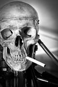 Closeup of a human skull on robot body with cigarette in mouth Stock Photos