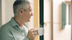 Pensive man drinking coffee at the window: thinking, look, hot, old Stock Footage