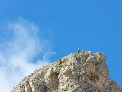 climbers on a hilltop with moon - stock photo