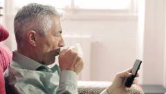 Cute man drinking coffee and typing on the phone: smart phone, mobile, web, call Stock Footage