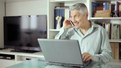 Beautiful man using computer in his office and use mobile phone: web, call, Stock Footage
