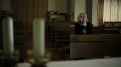 in the church: woman in background is praying: candles , catholics, faith, pray - stock footage