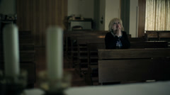 in the church: woman in background is praying: religion, catholics, faith, pray - stock footage