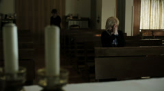 In the church: woman in background is praying: religion, catholics, faith, pray Stock Footage