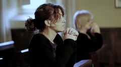 Intense prayer of two women in a church: religion, faith, devotion, Catholics Stock Footage
