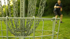 Disc Golf Player Throwing Into The Basket Stock Footage