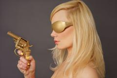 blonde lady holding a golden gun - stock photo