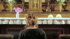 Sequence on young woman kneeling down in a christian church: praying, prayer Stock Footage