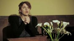 Sequence on young woman praying in a church with crossed hands: religion, prayer Stock Footage