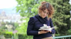 Beautiful woman reading book guide of Florence: turism, monuments, Italy, Tuscan Stock Footage