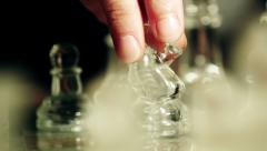 close up of glass chess playing: chessboard, moving pieces with finger, hand - stock footage