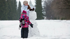 Caucasian mother with daughter making snowman at winter park Stock Footage