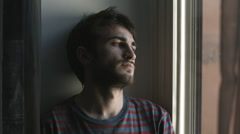 Young sad and depressed man looking out window Stock Footage