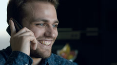 Smiling young and handsome man has change of mood during call at the phone: 4k Stock Footage