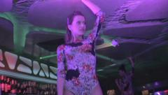 Sexy blond girl demonstrating hot body while dancing on bar, click for HD Stock Footage