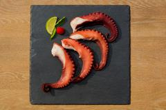 cooked octopus plate with lime in black stone background - stock photo