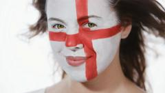 Female soccer fan with England flag on a face looking into a camera (closeup) Stock Footage